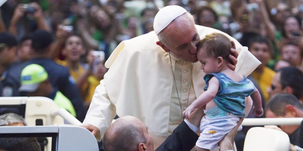 RIO DE JANEIRO, BRAZIL - JULY 22: Pope Francis kisses a baby while departing the Metropolitan Cathedral in the Popemobile after arriving in Rio on July 22, 2013 in Rio de Janeiro, Brazil. More than 1.5 million pilgrims are expected to join Pope Francis for his visit to the Catholic Church's World Youth Day celebrations. (Photo by Alexandro Auler/LatinContent/Getty Images)